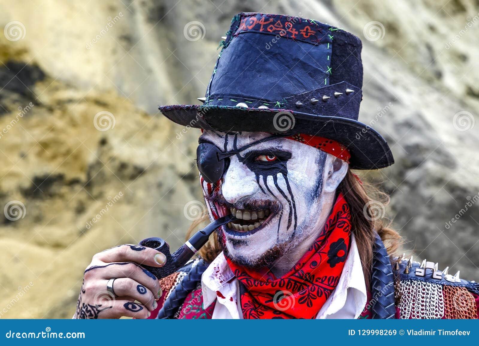Den giriga onda blicken av piratkopierar med lappen över ett öga och ett rör i hans mun