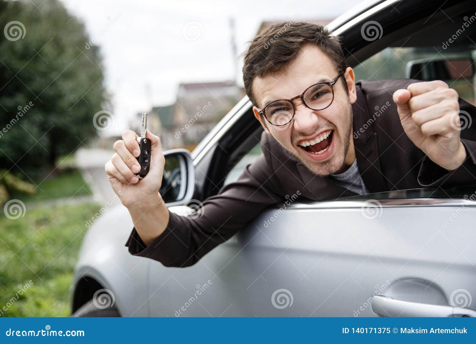Den gladde unga mannen kikar från bilfönstret, medan se kameran Han rymmer tangenterna på hans assistent hans