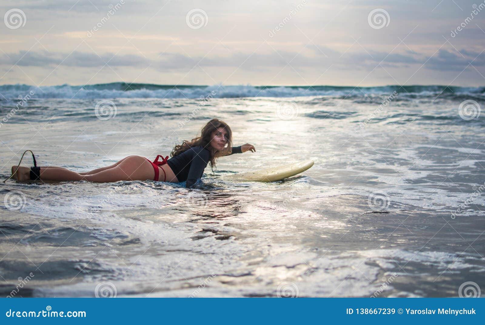 Den glade kvinnan har in gyckel, innan han surfar Surfareflicka med vita linjer maskering på hennes nätta bräde för framsidahållb
