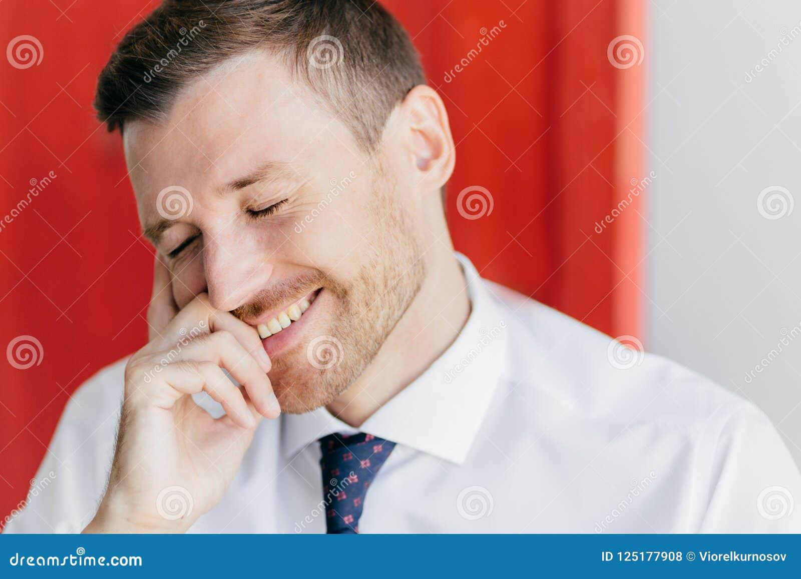 Den glade orakade mannen med det lyckliga uttryckt, fniss på det roliga skämtet, slut synar med nöje, den iklädda eleganta vita s