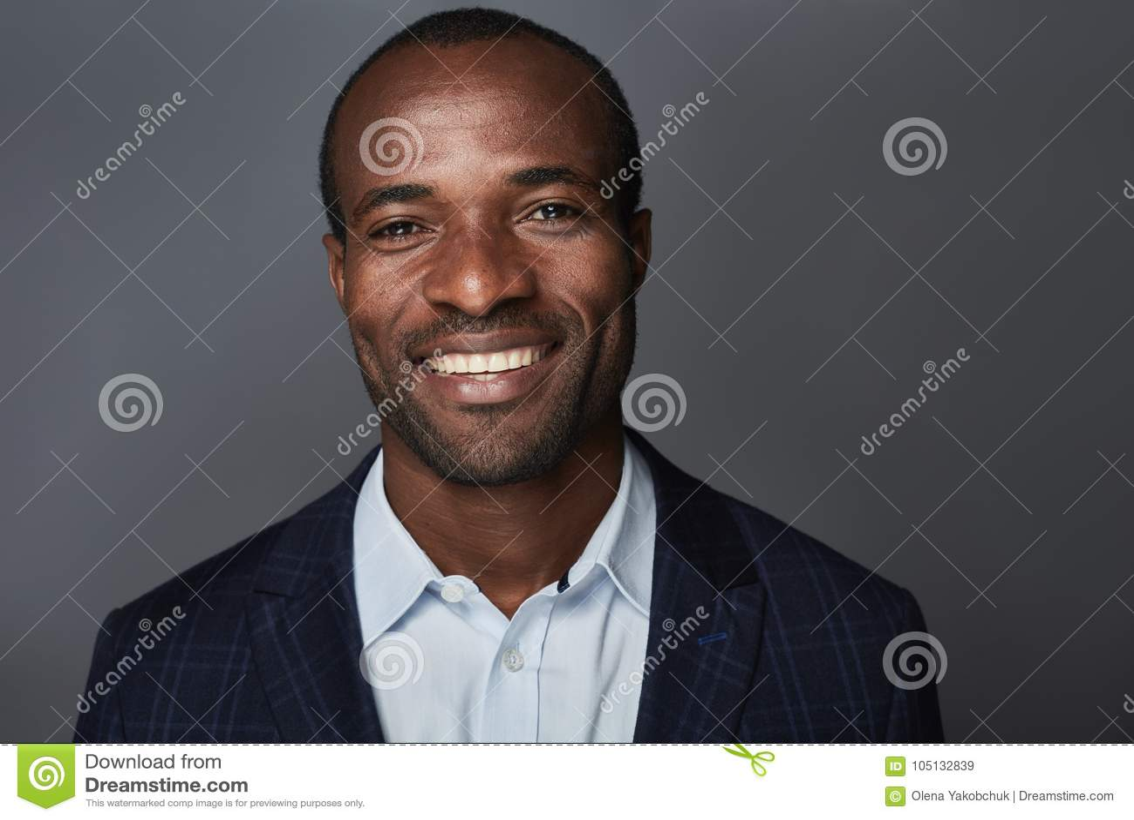 Den gladlynta affärsmannen i dräkt ler