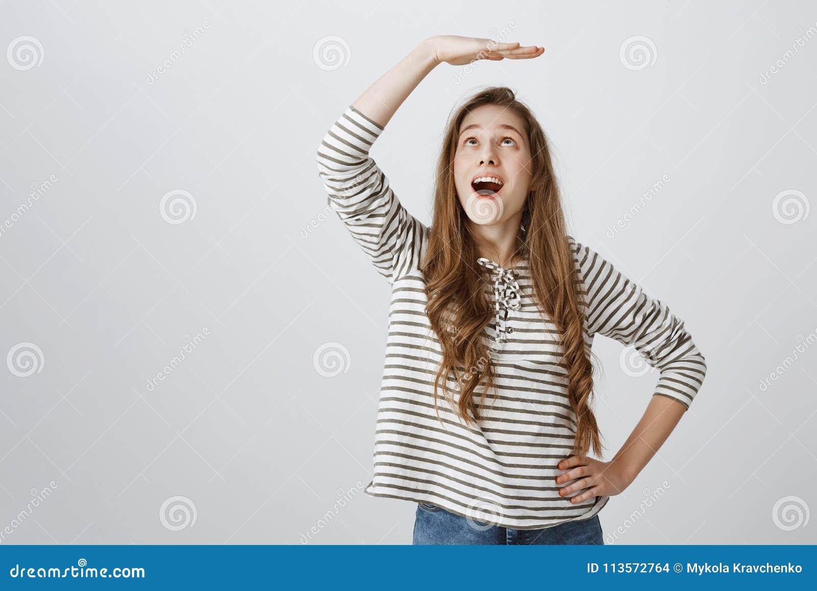 Den gladlynta flickan drömmer för att bli högt Ståenden av attraktivt skämtsamt lyfta för kvinna gömma i handflatan ovanför huvud