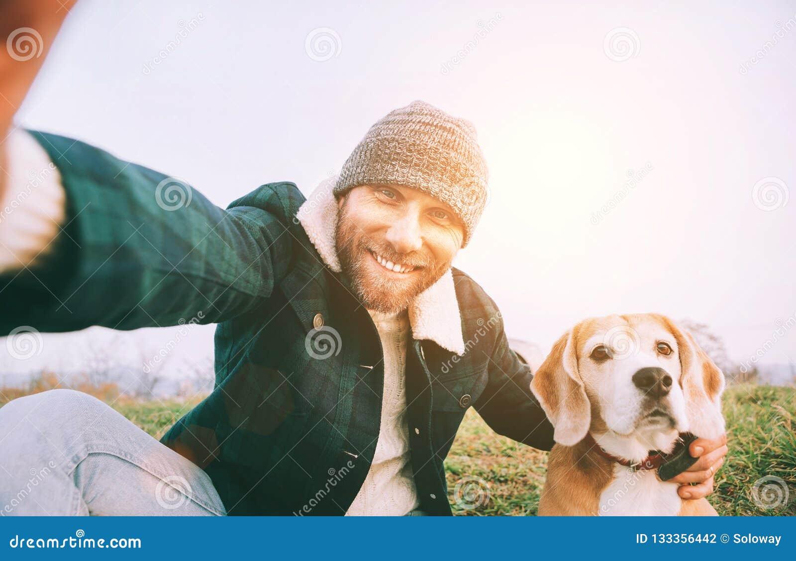 Den gladlynta le mannen tar selfiefotoet med hans bästa vänbea