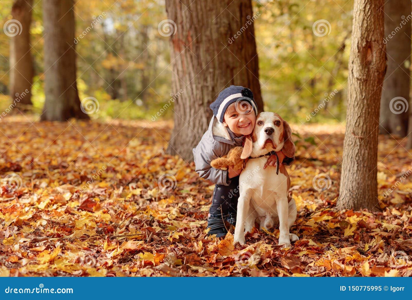 Den gladlynta lilla flickan kramar hennes hund