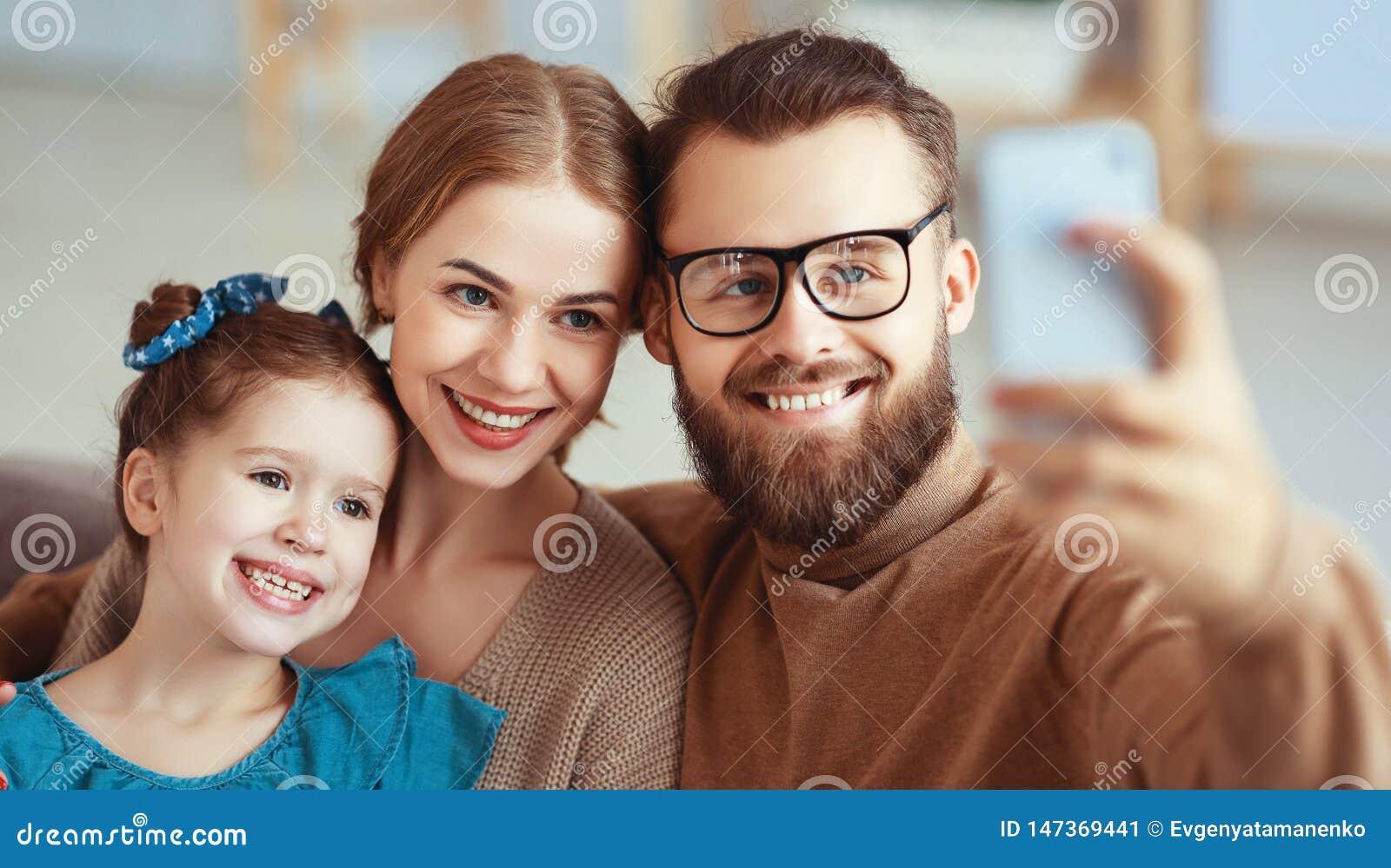 Den gladlynta lyckliga det familjmoderfadern och barnet tar selfies, tar bilder