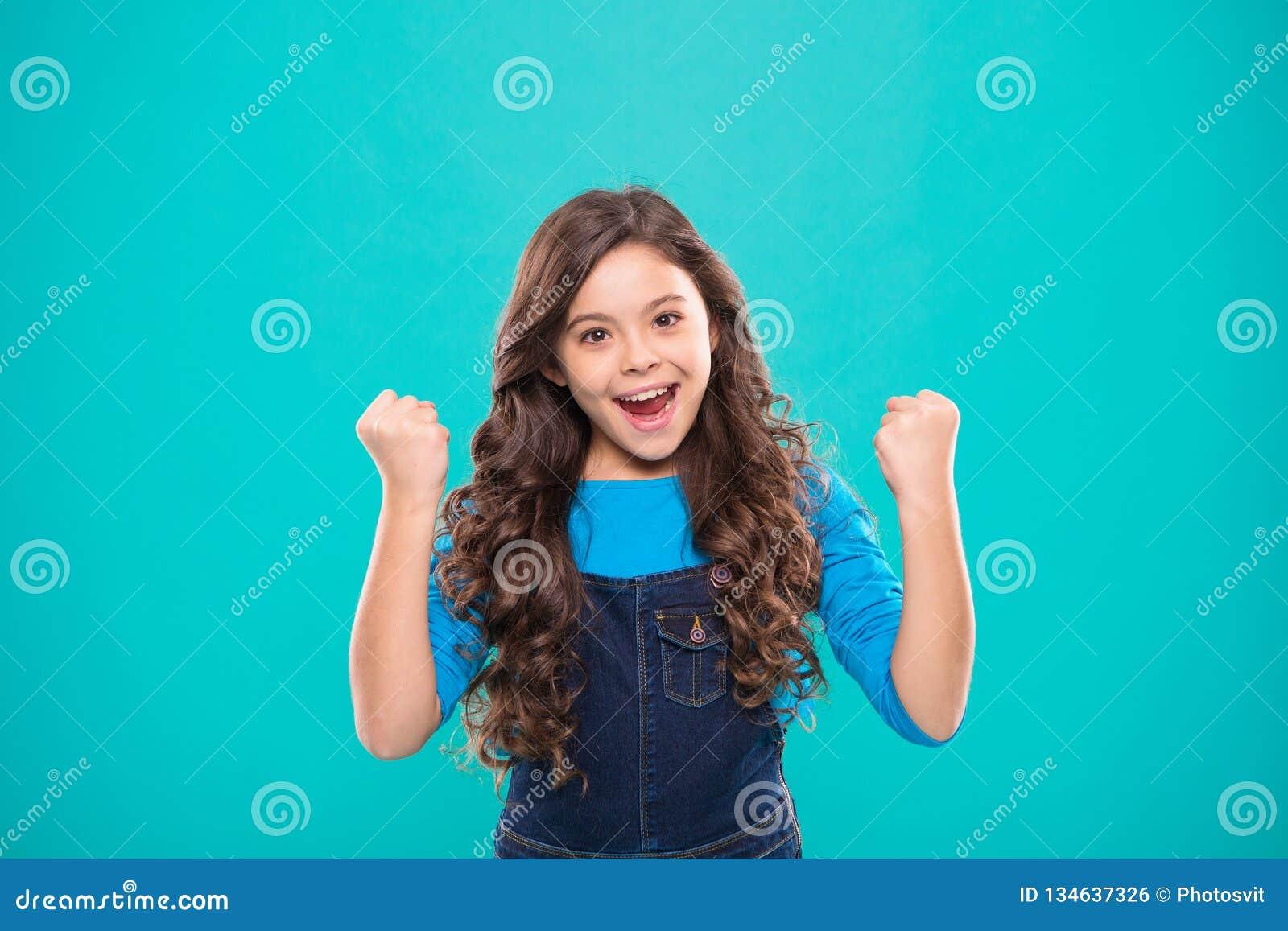 Den gladlynta ungen firar seger Le för lockigt hår för gulligt barn för flicka långt lyckligt Barnpsykologi och utveckling Lyckli