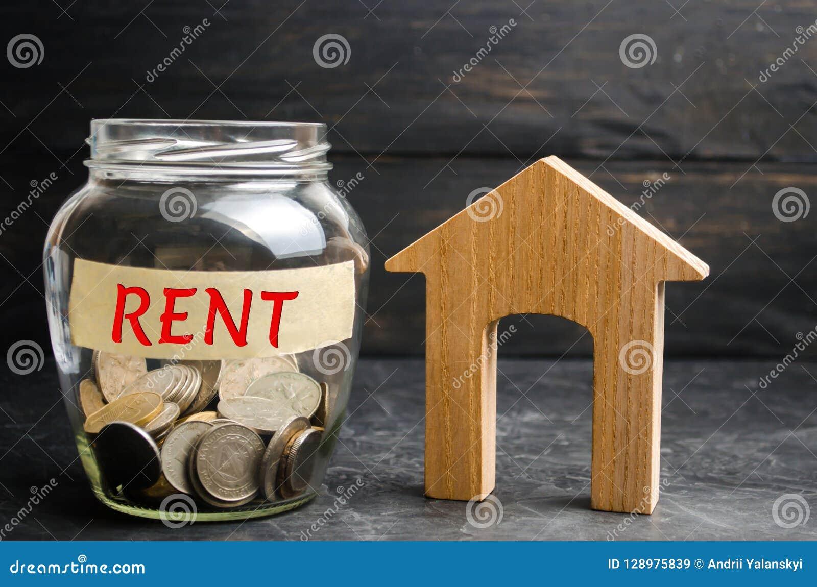 Den Glass kruset med mynt och inskrift`en hyr ` och ett litet trähus Hyra av egenskapen, lägenheter service av en fastighetsmäkla