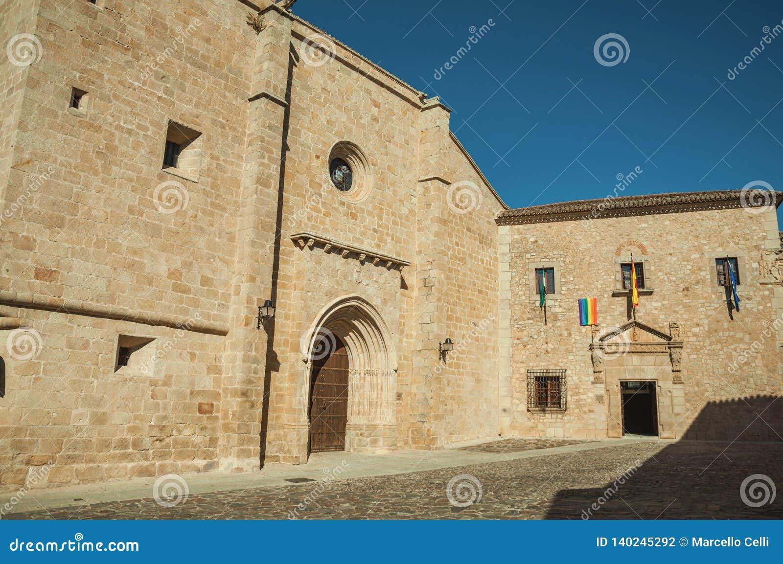 Den gotiska Santa Maria Cathedral och den gamla byggnaden med flaggor på Caceres