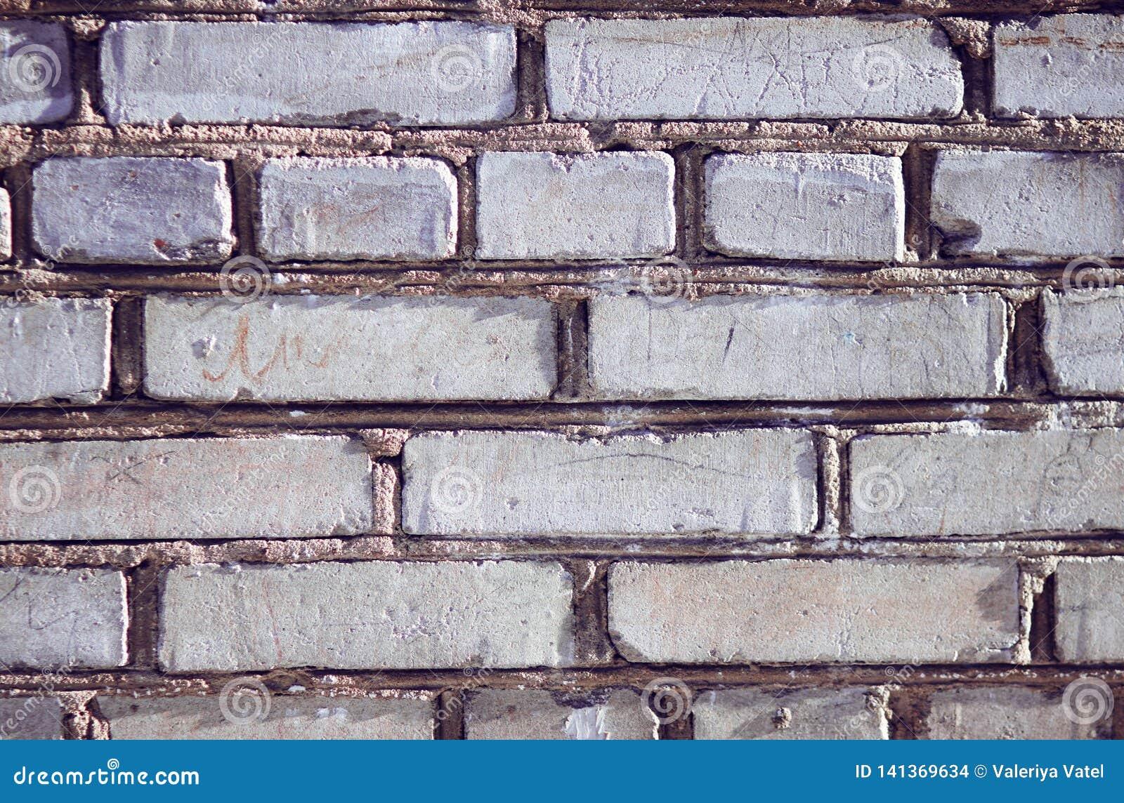 Den gråa väggen av byggnaden som byggs av grova ojämna tegelstenar