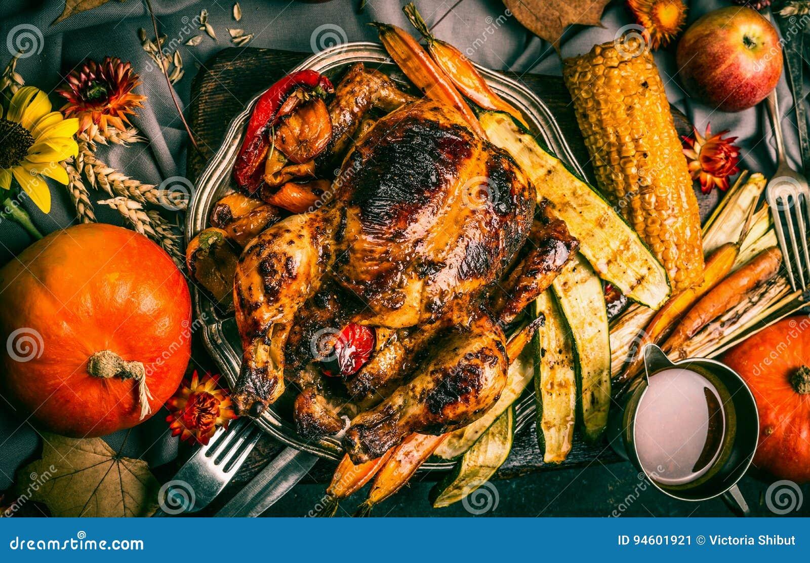 Den grillad välfylld hel kalkon eller höna med organisk skördgrönsaker och pumpa för tacksägelsematställe tjänade som på lantlig