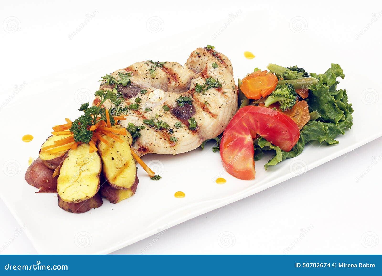 Den grillade fisken tjänade som med potatisar, morötter och tomater Peruansk maträtt
