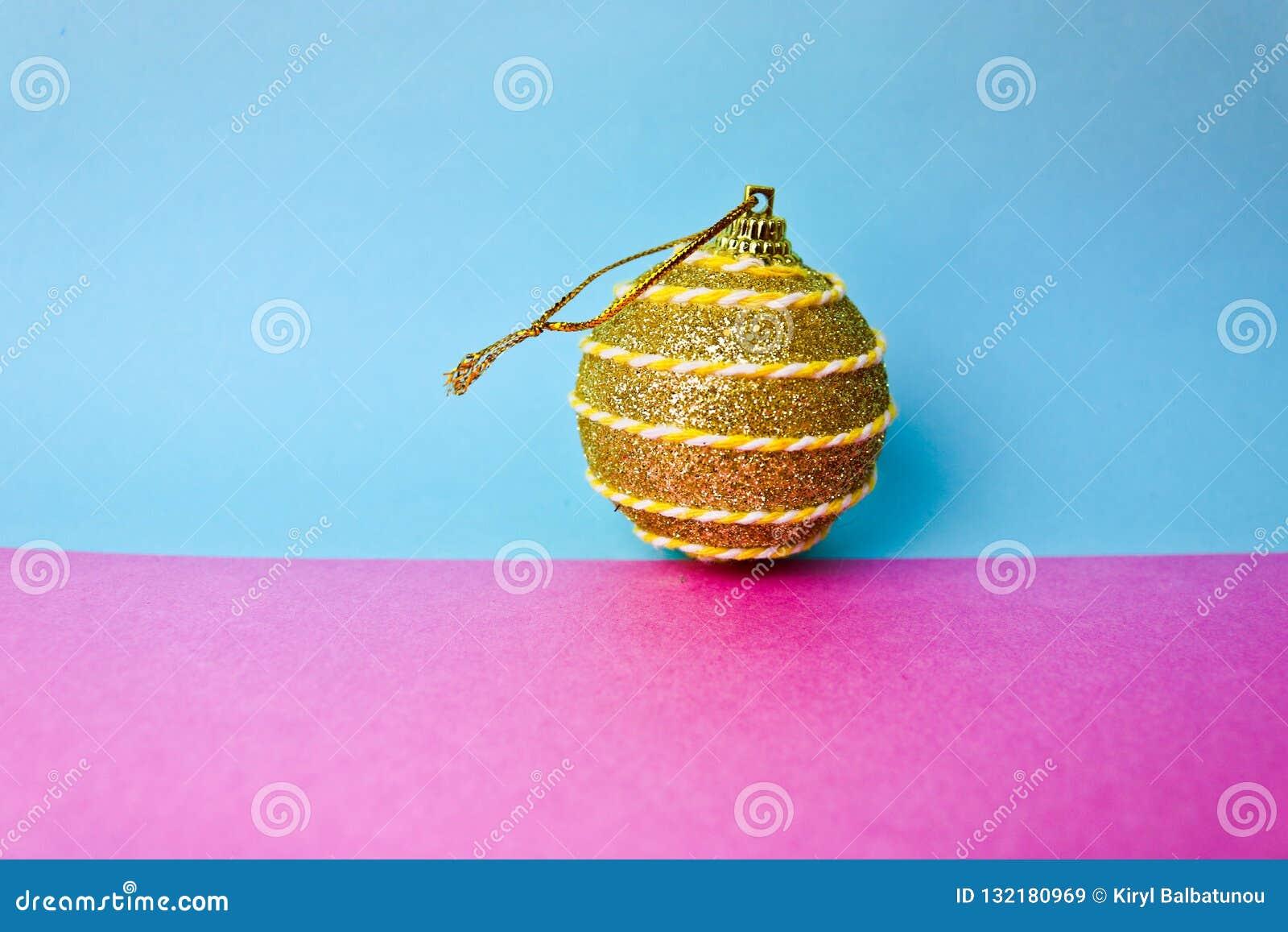 Den gula guld- bollen för jul för xmas för den lilla rundan festliga, julleksaken som över rappas, mousserar på en rosa purpurfär