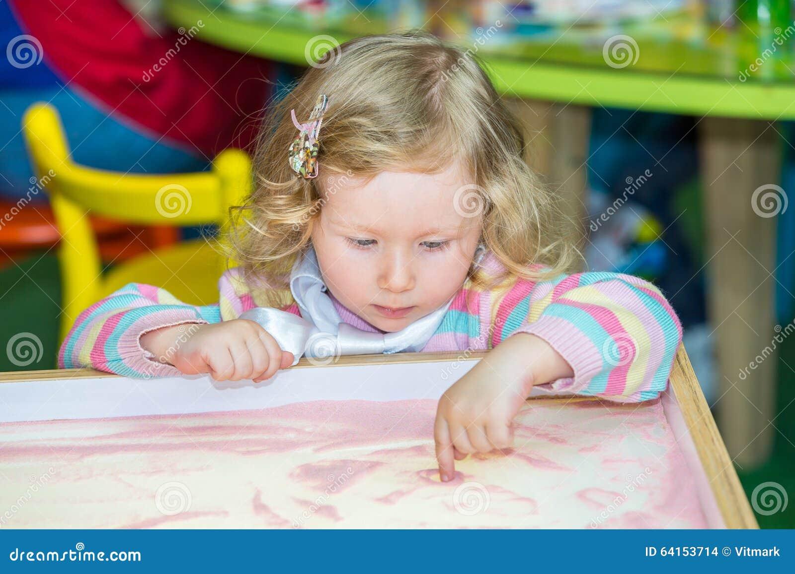 Den gulliga barnflickateckningen drar framkallande sand i förträning på tabellen i dagis