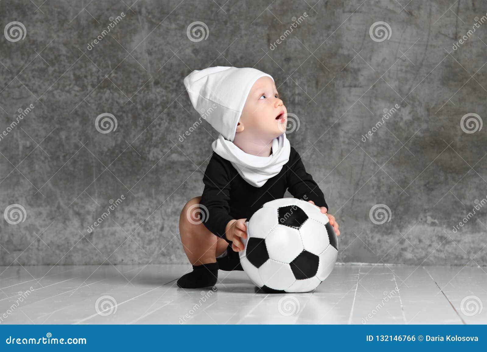 Den gulliga bilden av behandla som ett barn rymma en fotbollboll