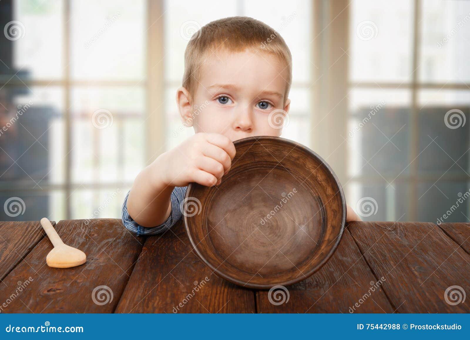 Den gulliga blonda pojken visar den tomma plattan, hungerbegrepp