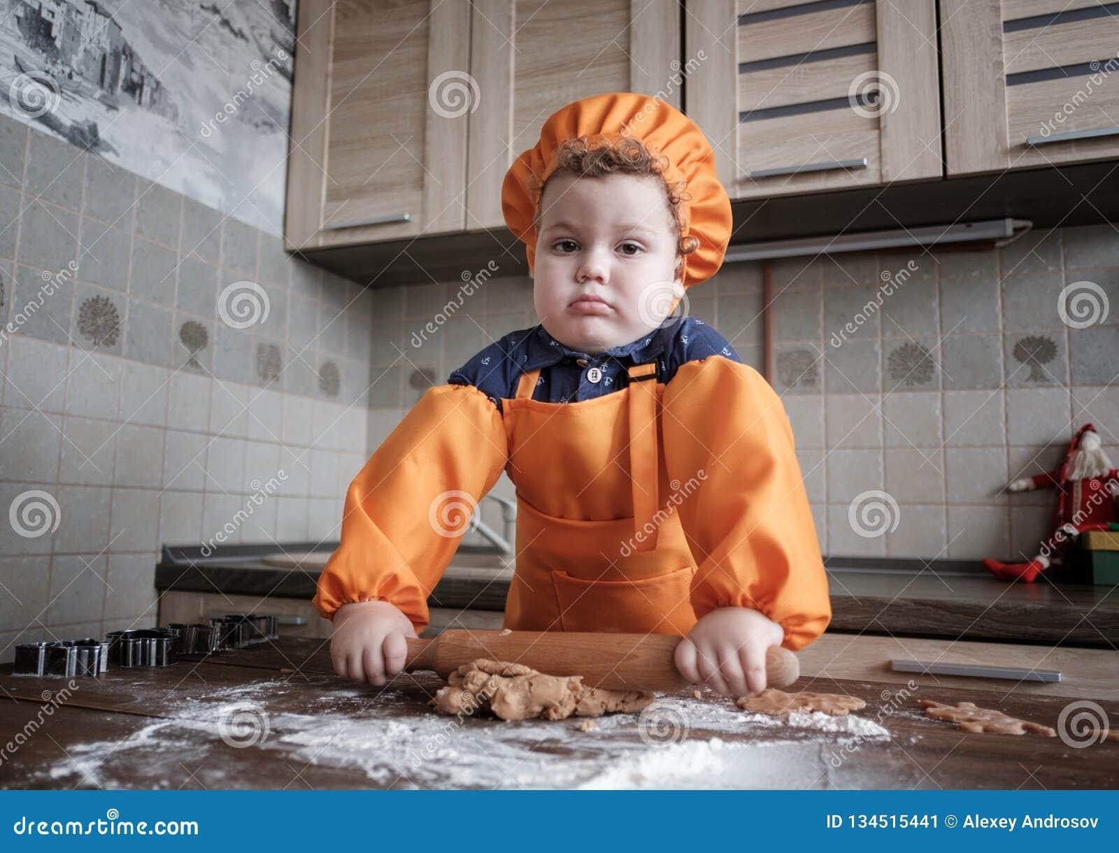 Den gulliga europeiska pojken i en dräkt av kocken gör ljust rödbrun kakor
