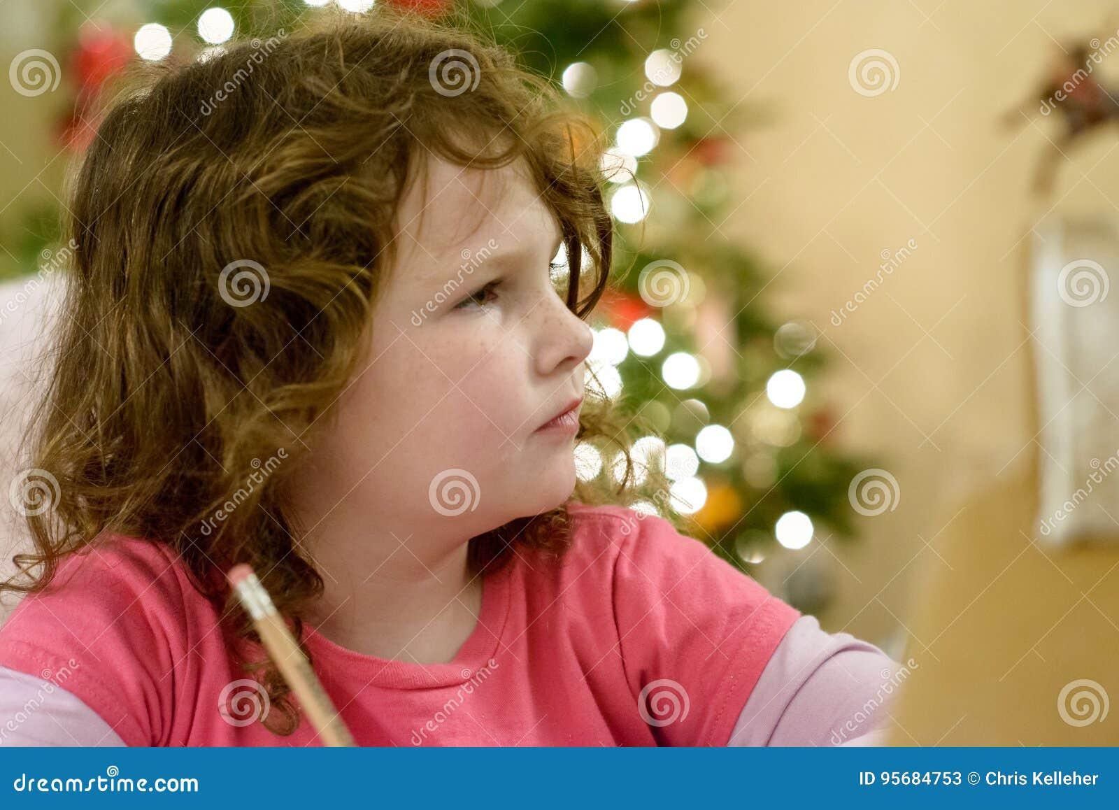 Den gulliga flickan för det lilla barnet skrivar brevet till Santa Claus nära julgranen inomhus
