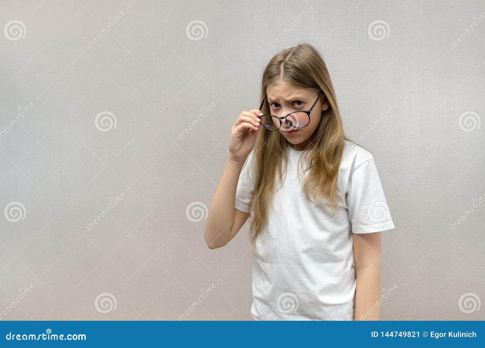 Den gulliga flickan med exponeringsglas ser med en misst?nksam blick Tvivel misstro, ?verraskning