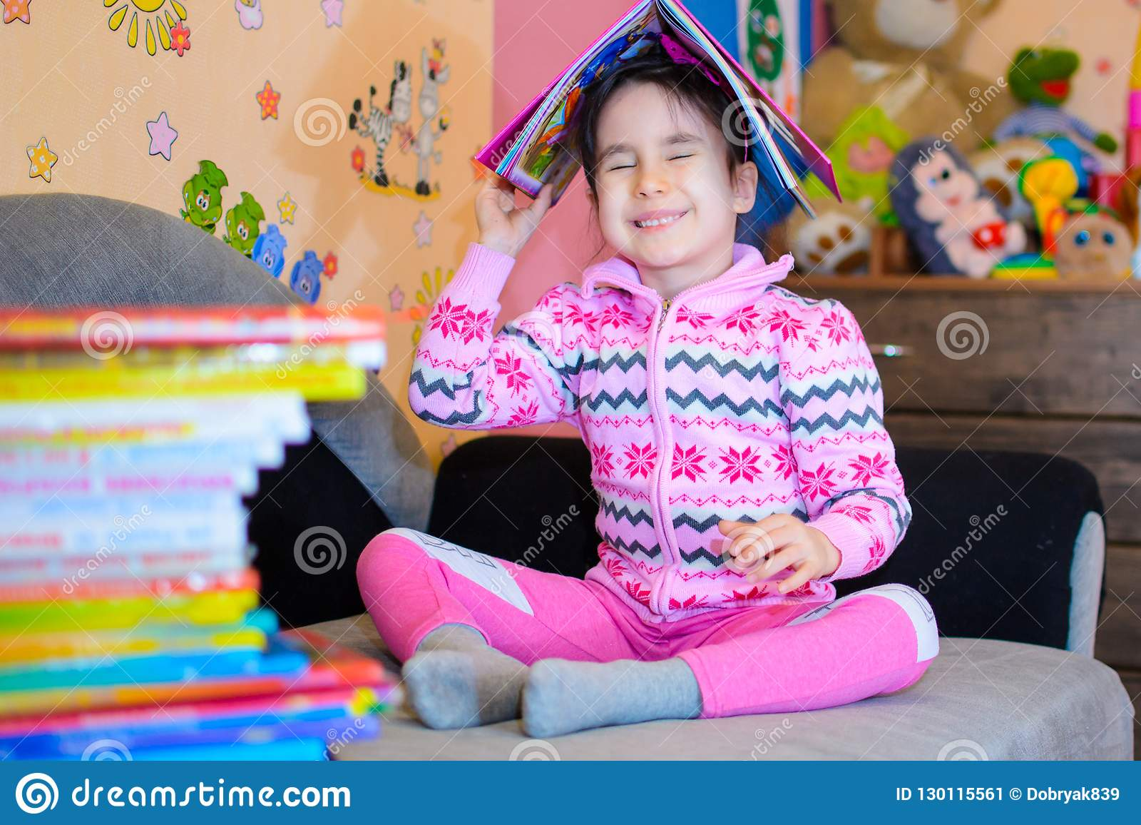Den gulliga flickan på bakgrunden av henne leker med en bok