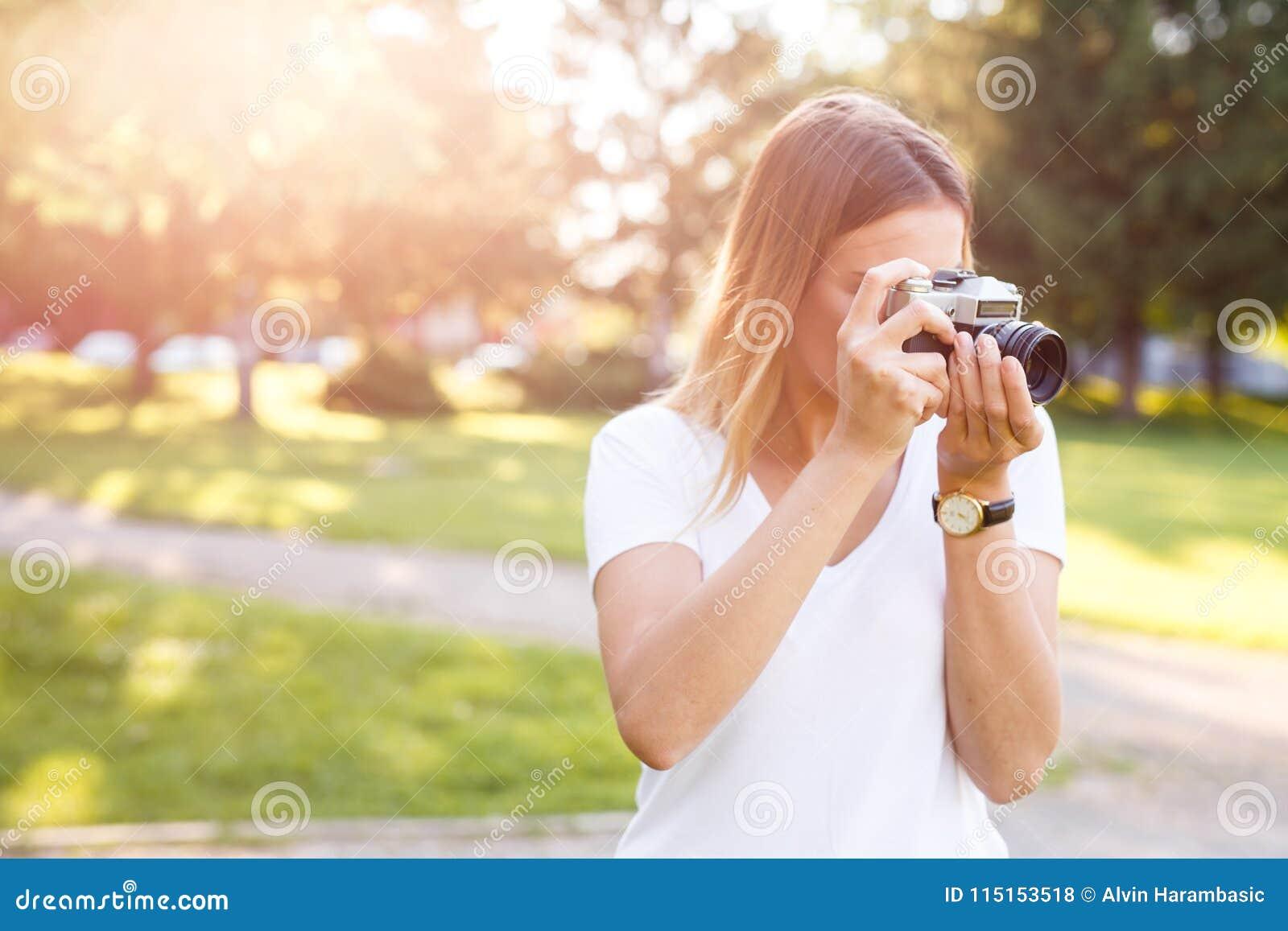 Den gulliga flickan på solig dag i parkering som tar foto med motsvarighet, kom