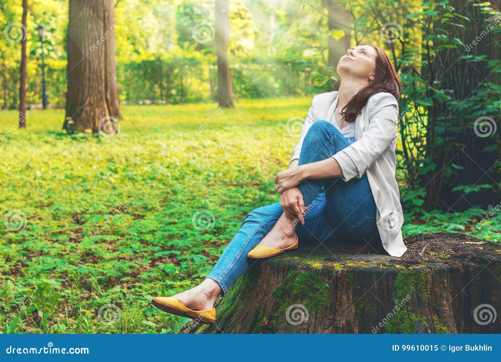 Den gulliga kvinnan är att tycka om av den pittoreska naturen Vila den härliga flickan sitter på en stor gammal stubbe i skogen,