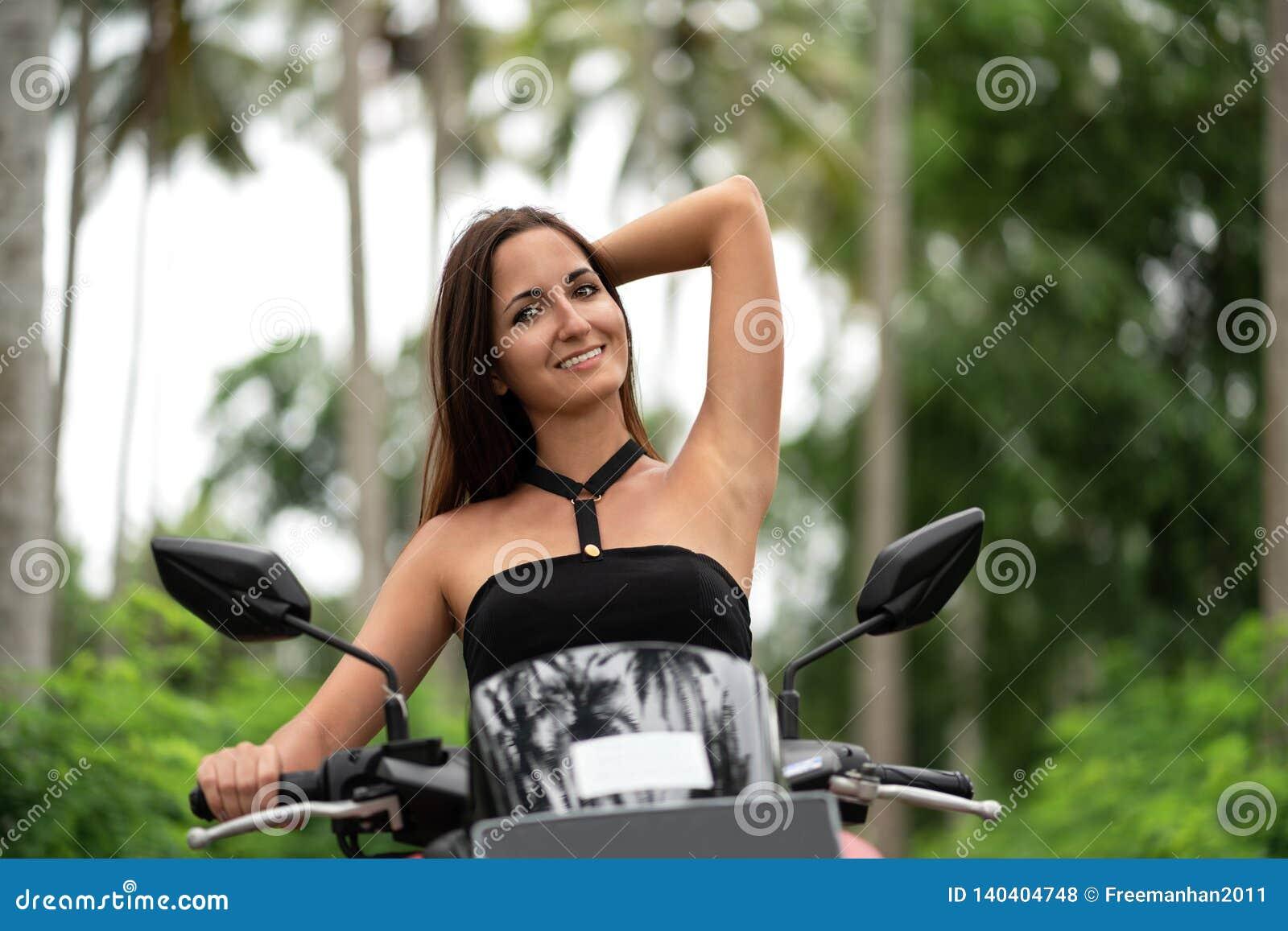 Den gulliga kvinnan ler och rätar ut hennes hår som sitter bak hjulet av en sparkcykel
