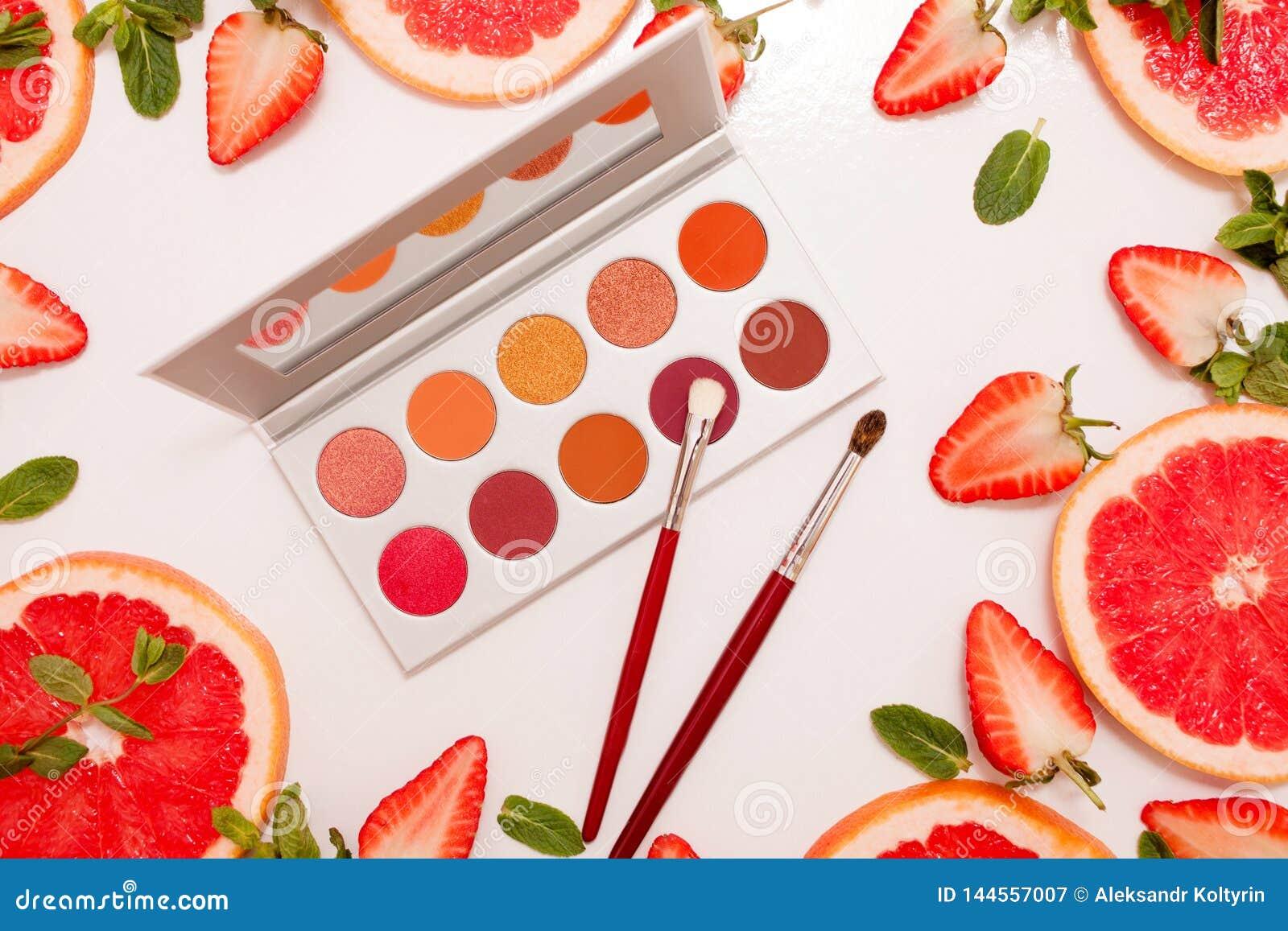Den gulliga lägenheten lägger med paletten av skönhetsmedel med ny frukt, den klippta jordgubbar och grapefrukten eller den röda