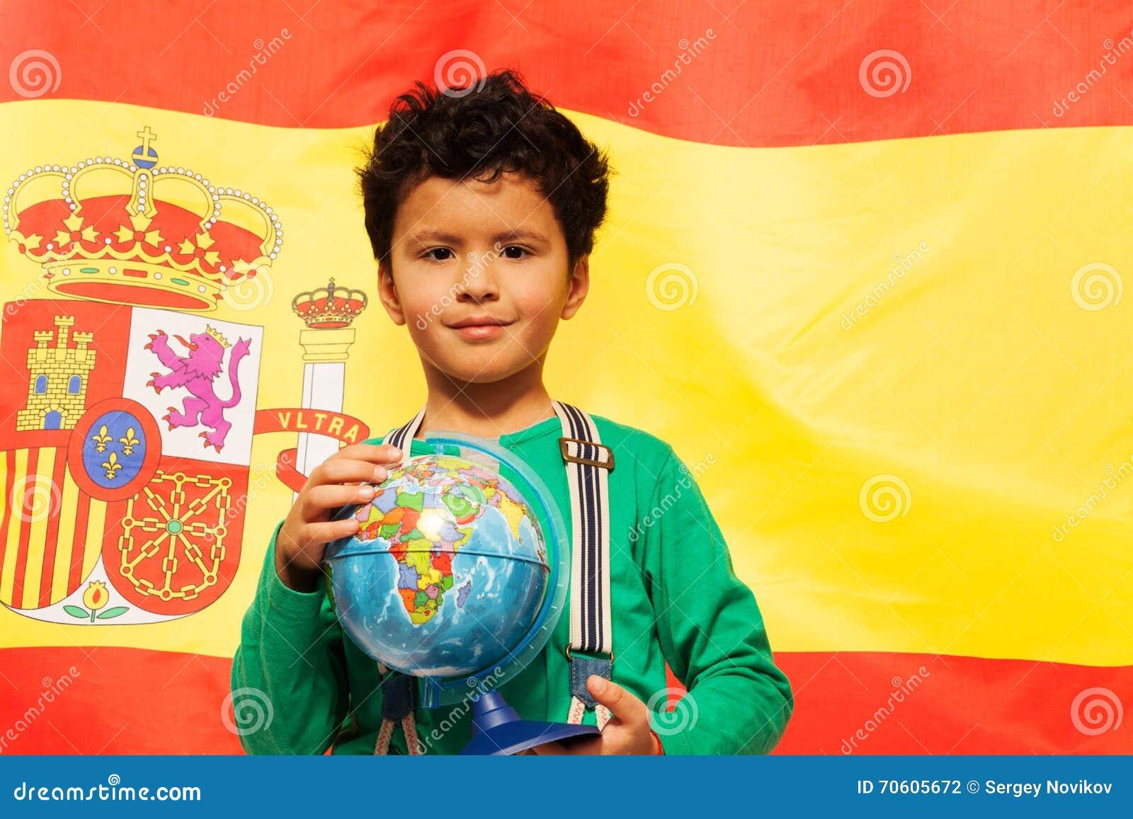 Den gulliga latinamerikanska pojken lär geografi med jordklotet