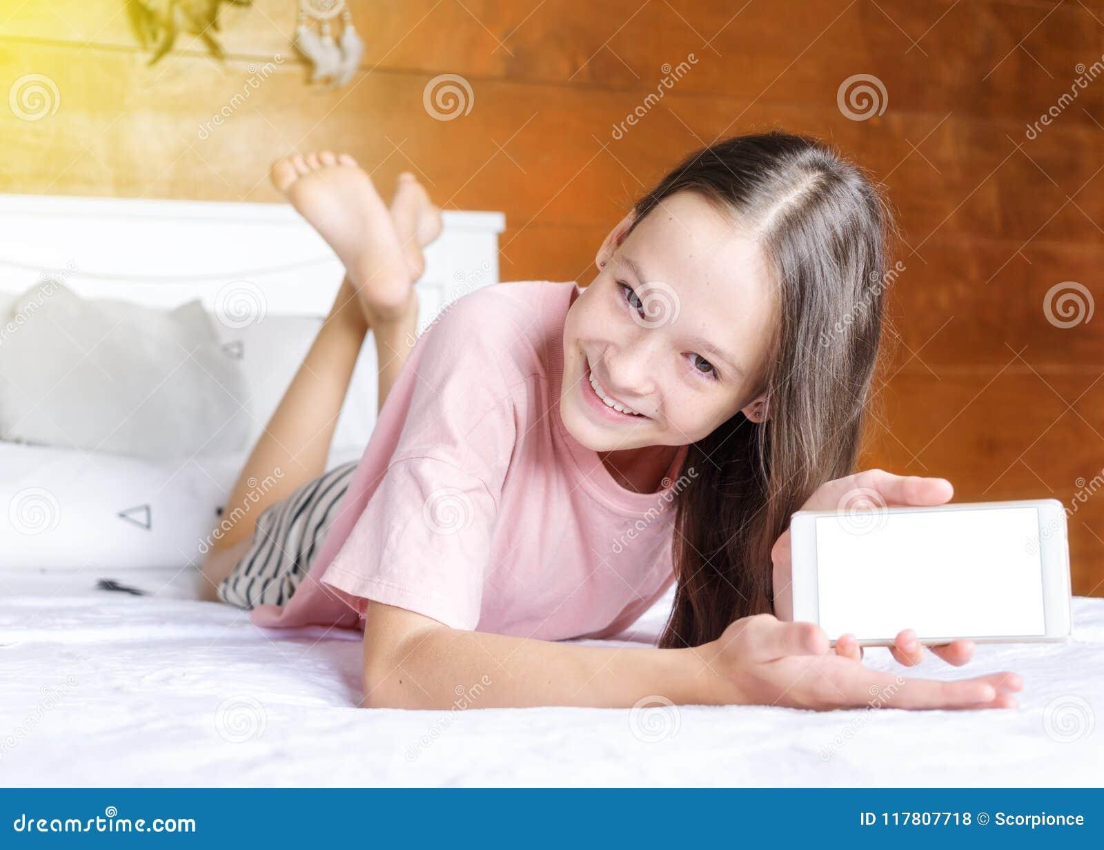Den gulliga le preteenflickan i rosa t-skjorta och kortslutningar på säng visar hennes mobiltelefonskärm i bohostilrum mot den ga