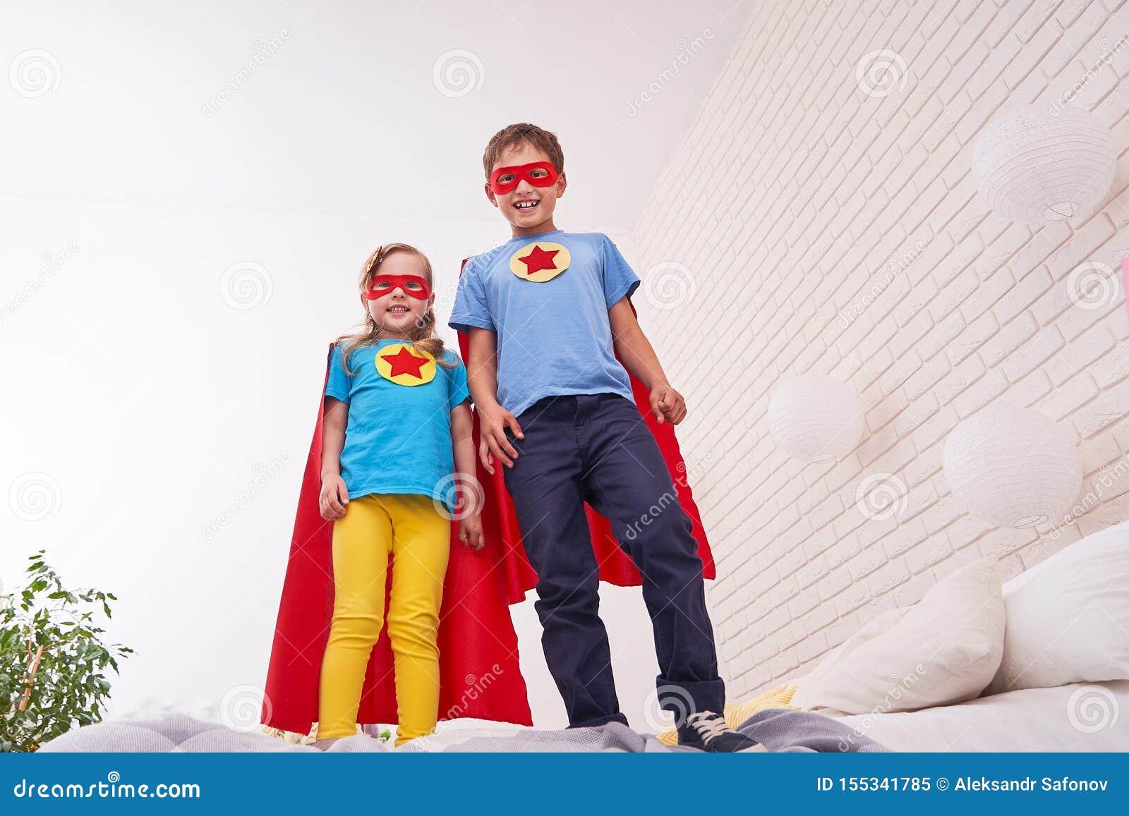Den gulliga lilla flickan och pojken står på sängen som får klar att flyga, spela superheroen med kappan och maskeringen hemma i