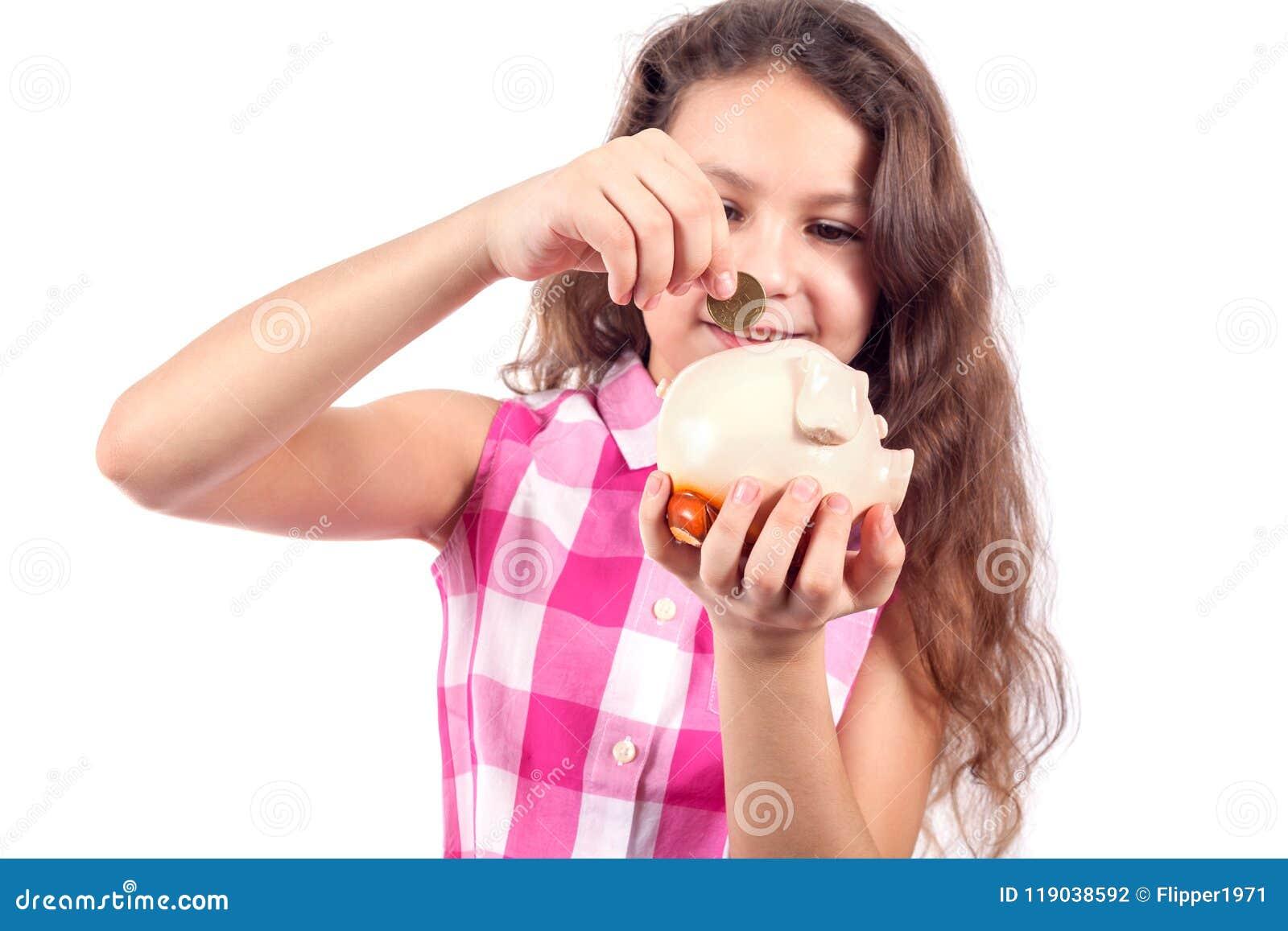 Den gulliga lilla flickan sätter ett mynt i enpiggy bank