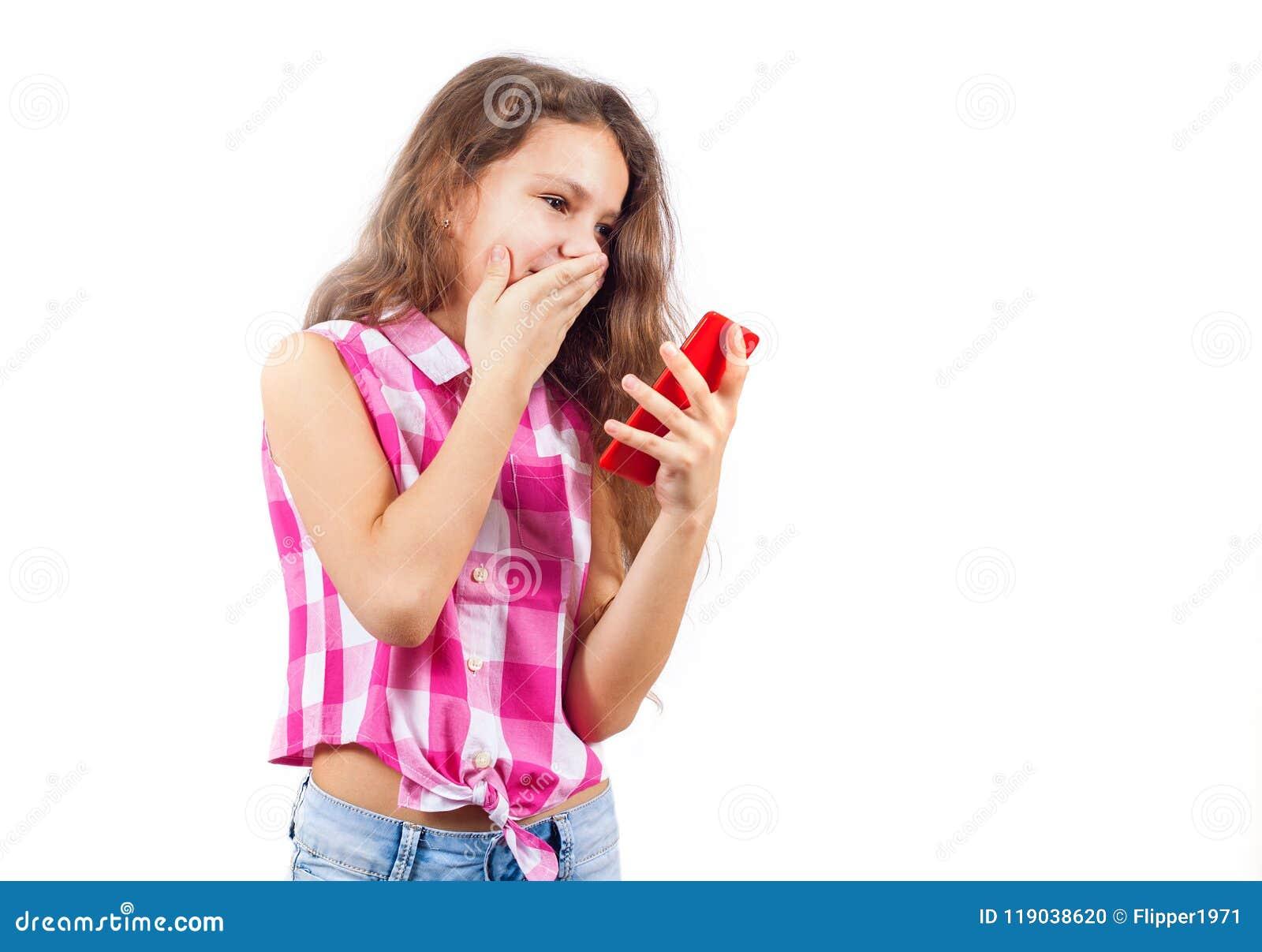 Den gulliga lilla flickan ser i smartphone och täcker hennes mun i sur