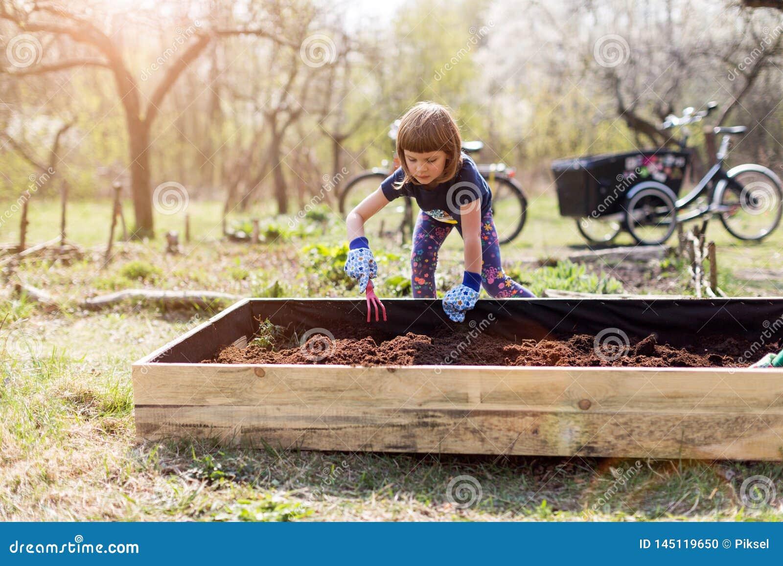 Den gulliga lilla flickan tycker om att arbeta i trädgården