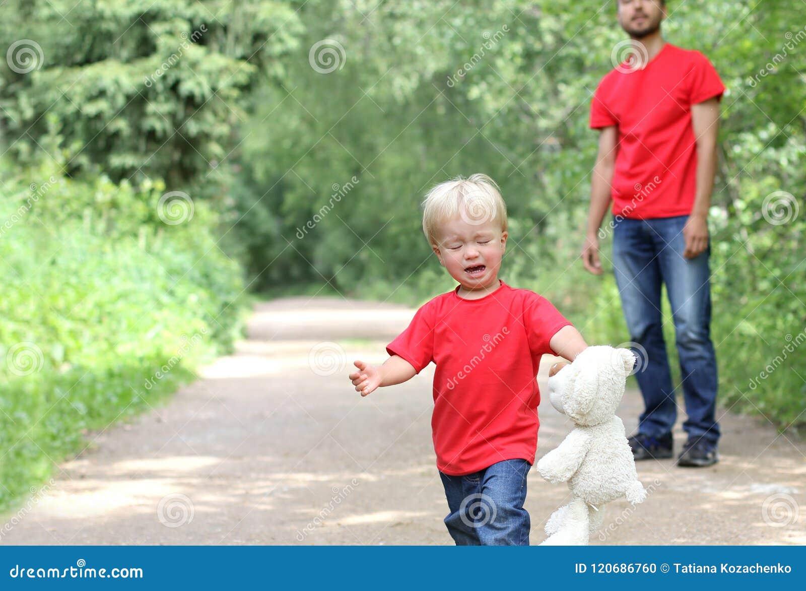 Den gulliga litet barnpojken med en nallebjörn i hans armar gråter Farsan står bakom Barnuppfostransvårighetsbegrepp Familjblickk