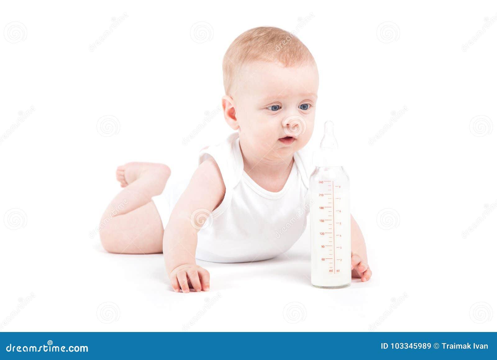 Den gulliga lyckliga pysen i den vita skjortan nära mjölkar flaskan