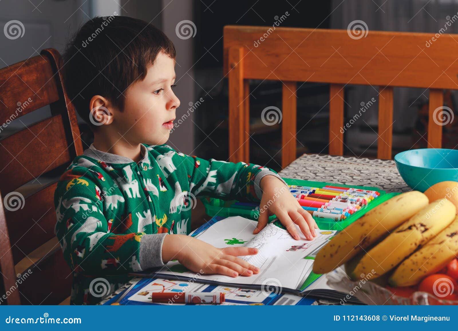 Den gulliga pojken drar och gör applikationer på albumark efter dinn