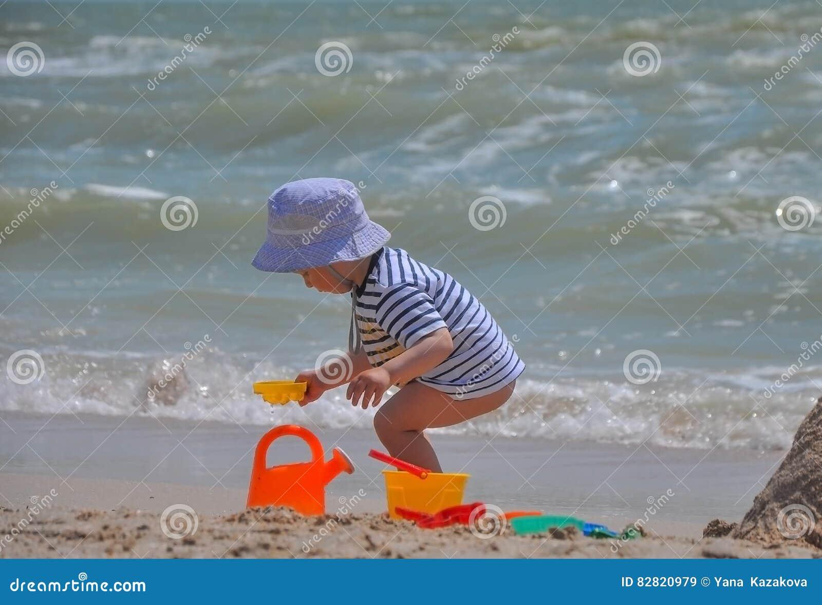 Den gulliga pojken spelar en hink på stranden