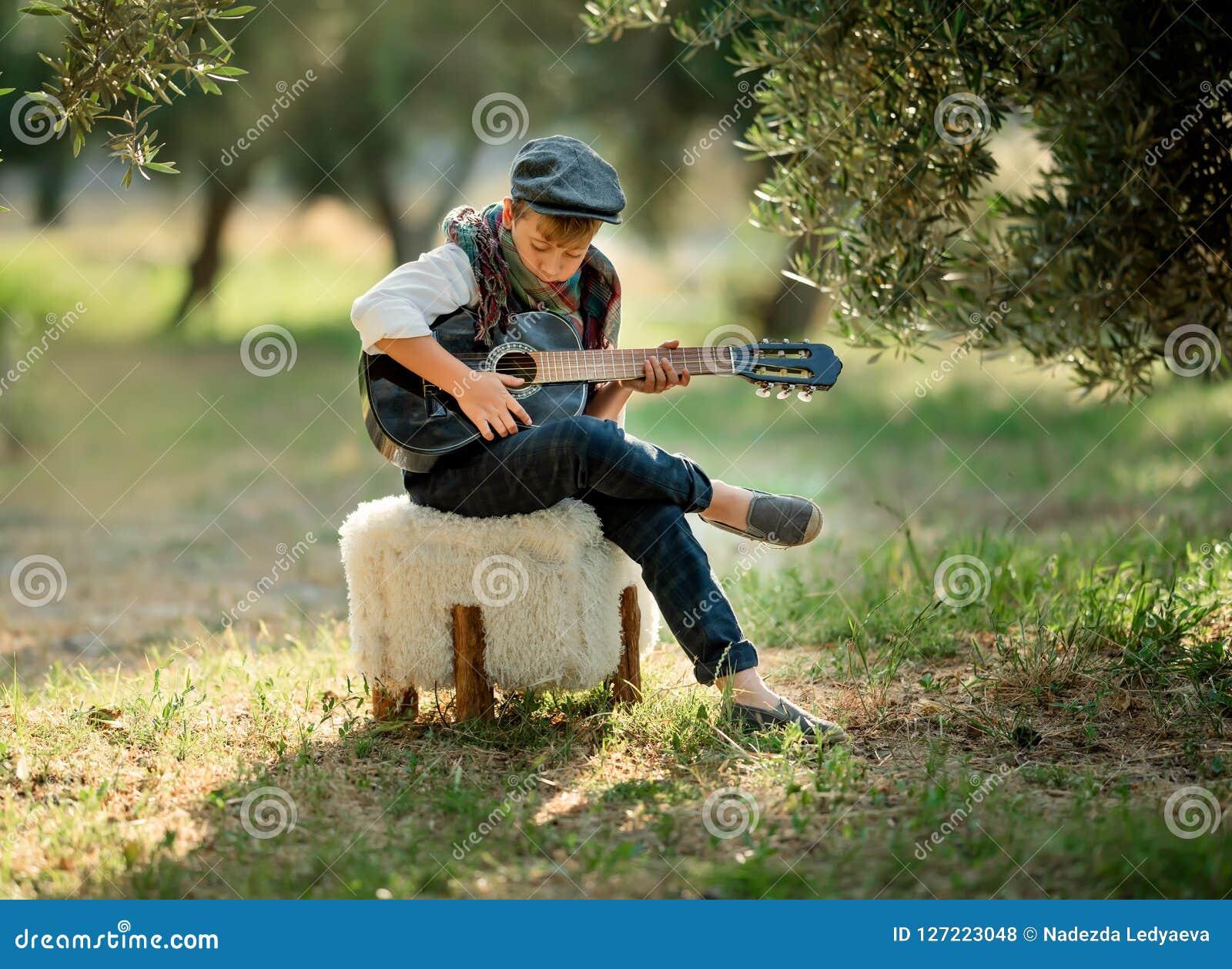Den gulliga pysen spelar gitarren i parkera