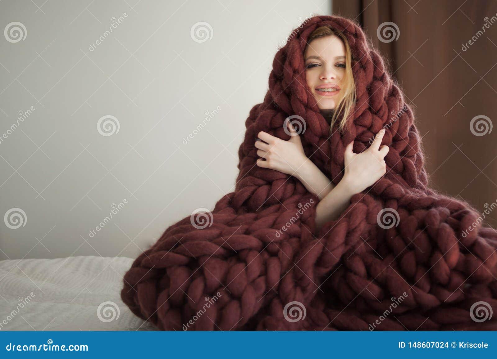 Den gulliga unga kvinnan sitter p? s?ngen som sl?s in i en stor och fluffig brun pl?d V?rme och komfort av hemmet
