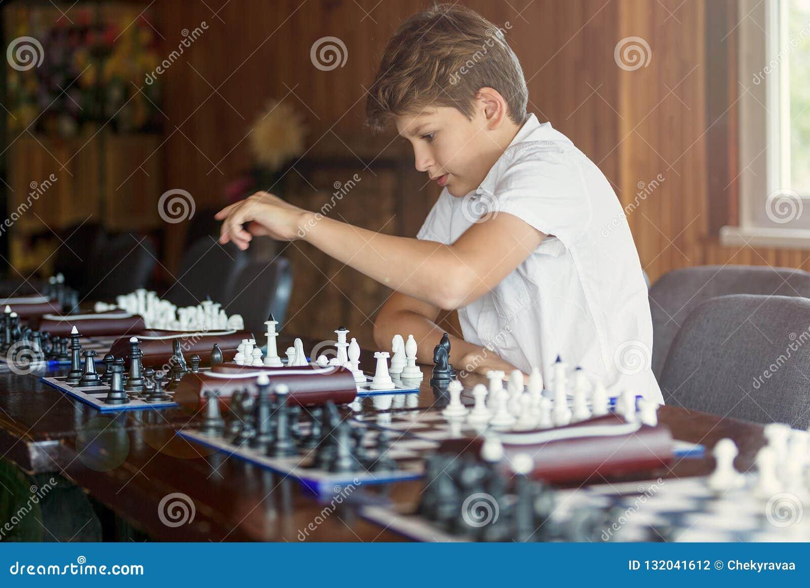 Den gulliga unga pojken spelar schack med träschackbrädet Schackturnering, kurs, läger, utbildning