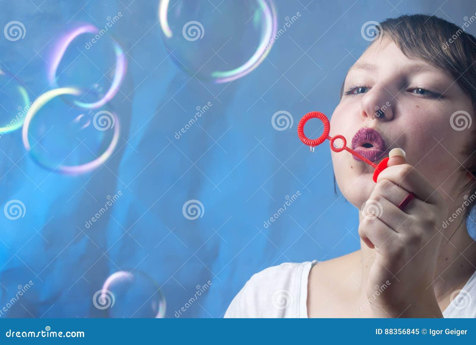Den härliga älskvärda flickan blåser såpbubblor på en härlig blått