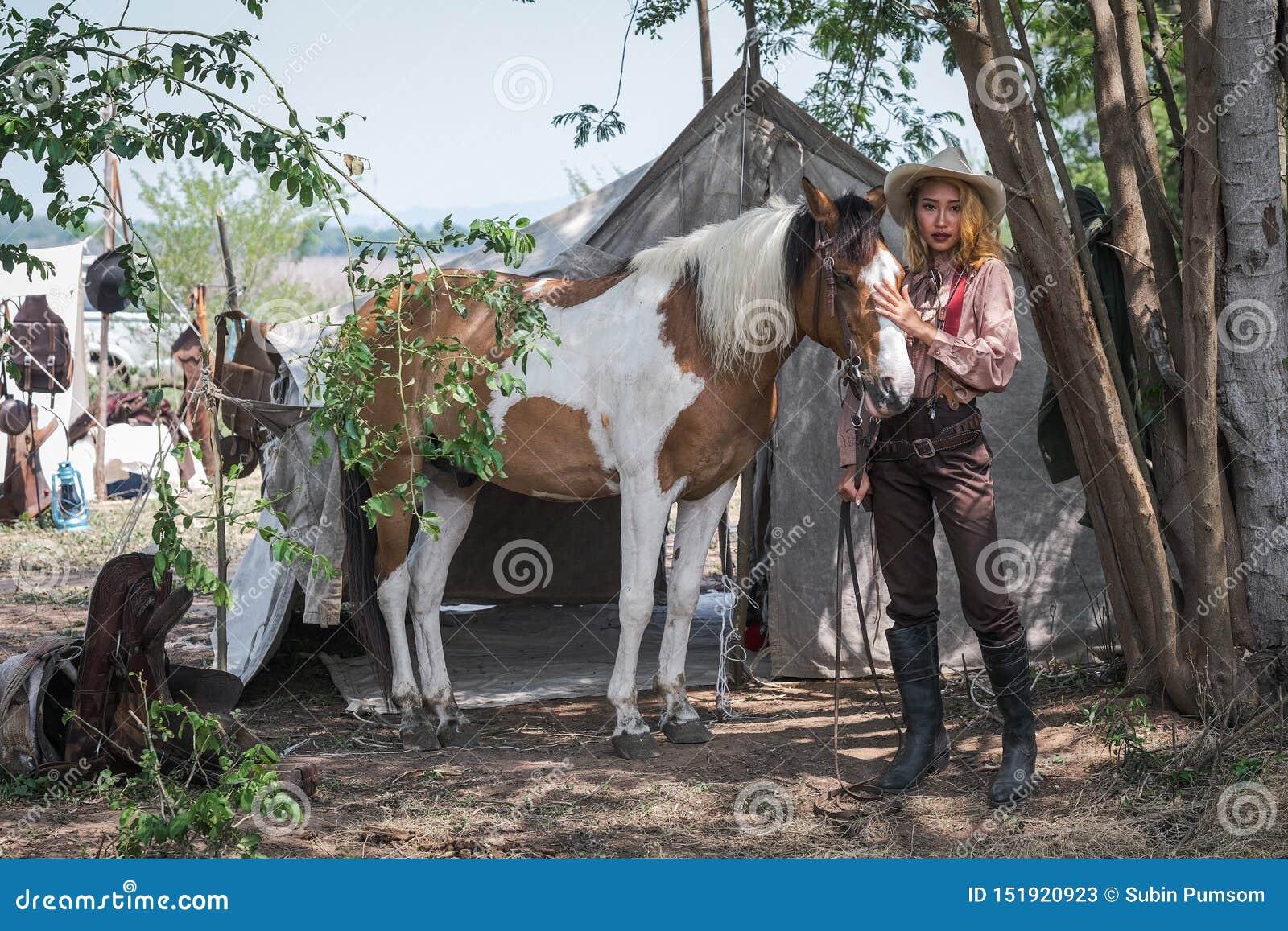 Den härliga asiatiska flickacowboyen tar omsorg av hennes häst med förälskelseomsorg