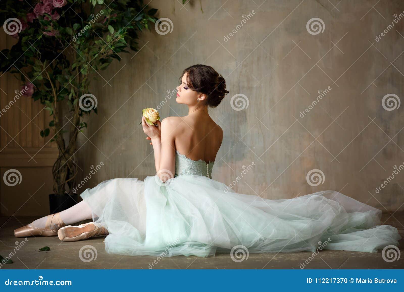 Den härliga behagfulla flickaballerina i en luftklänning och pointe sitter