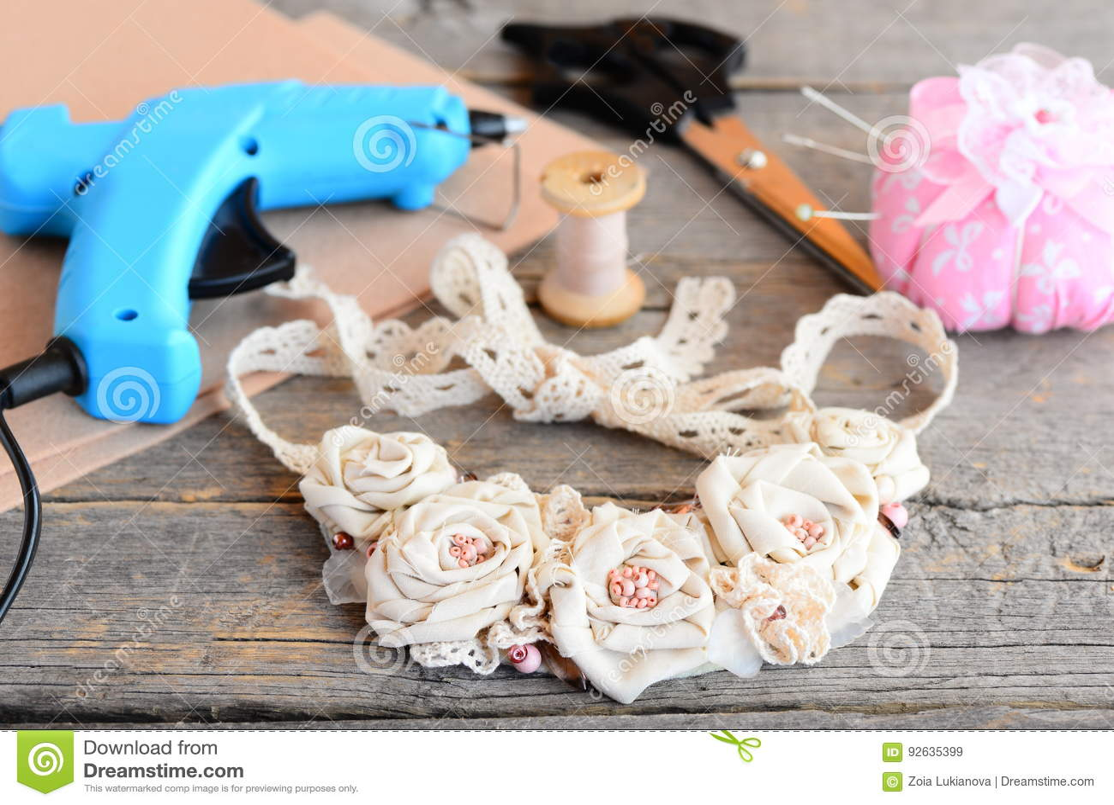 Den härliga blommatyghalsbandet, limmar det varma vapnet, sax, tråden, visaren, filt på tappningen trätabell Skapa en halsband