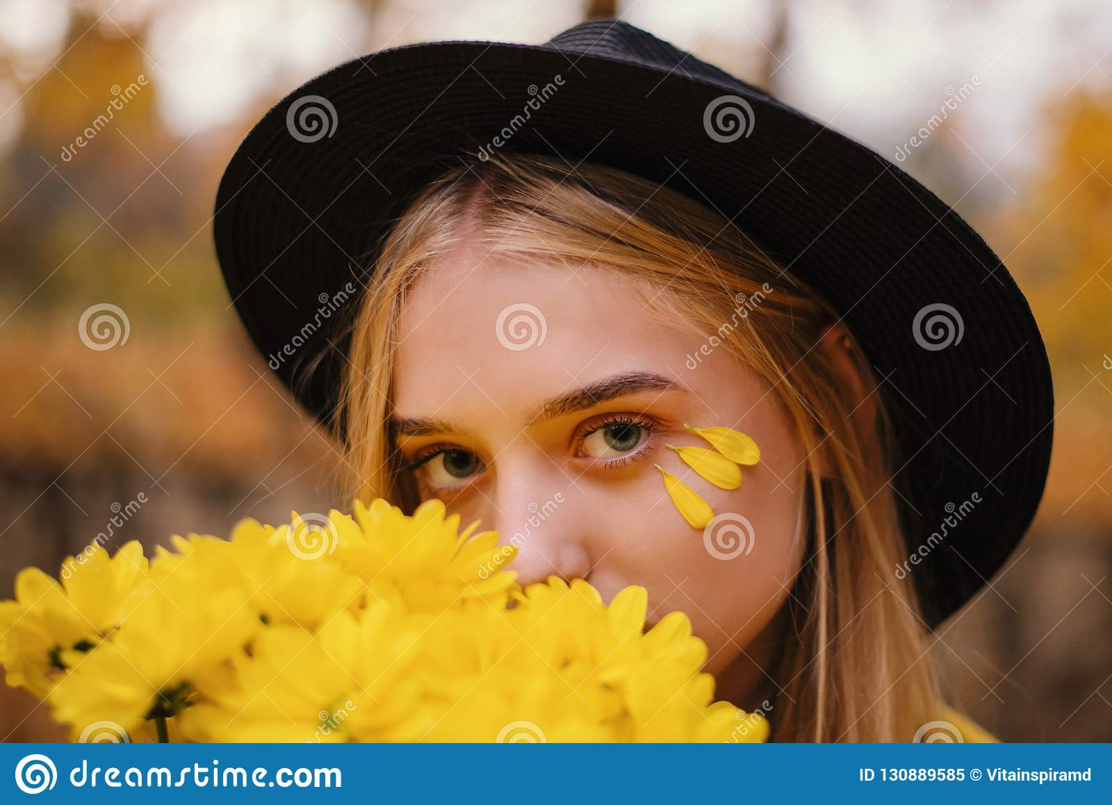 Den härliga blonda flickan i en hatt med buketten av gula blommor i höst parkerar fullt av gula sidor
