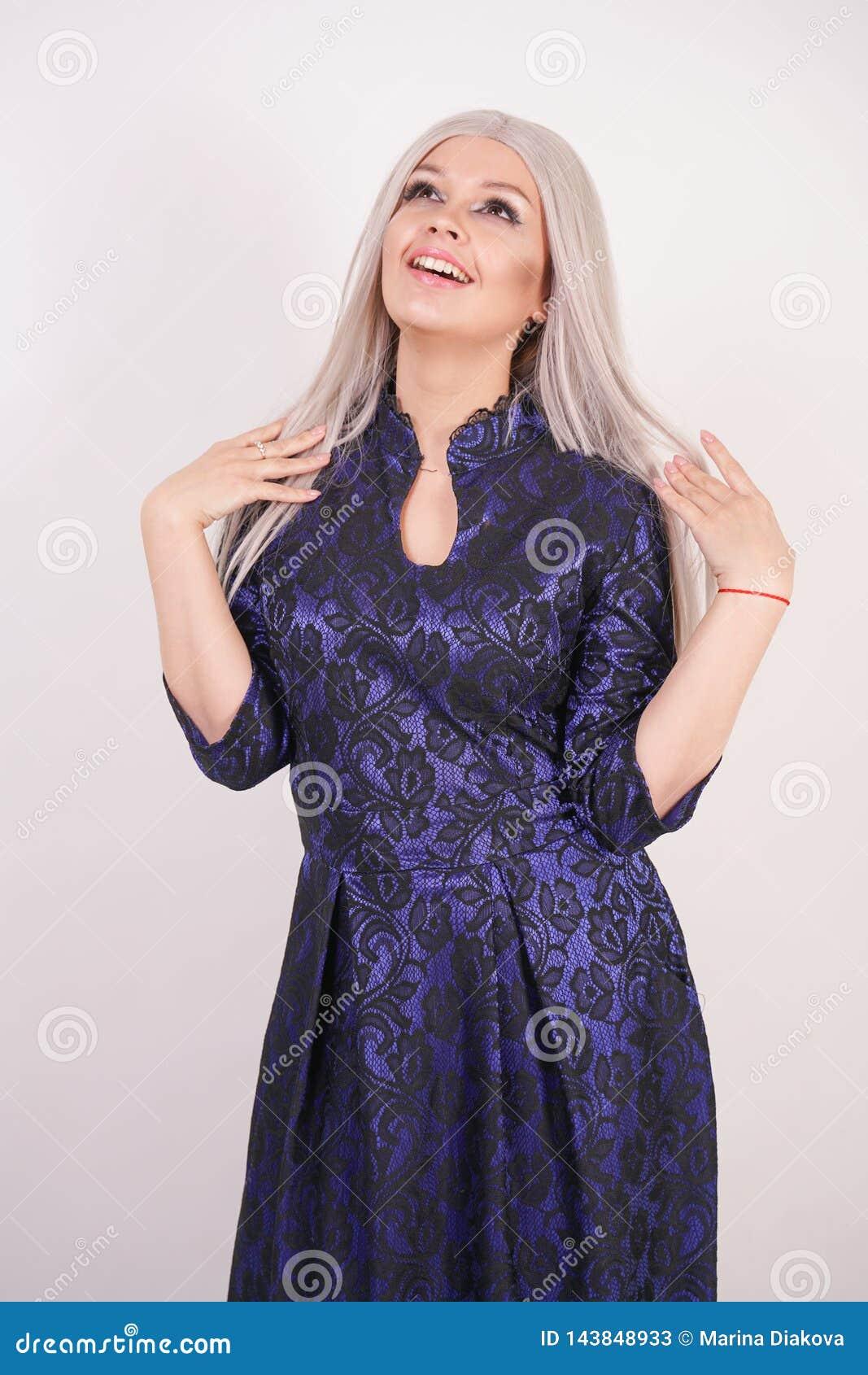 Den härliga blonda flickan i lyxiga blått med svart snör åt aftonklänningen på vit bakgrund i studio