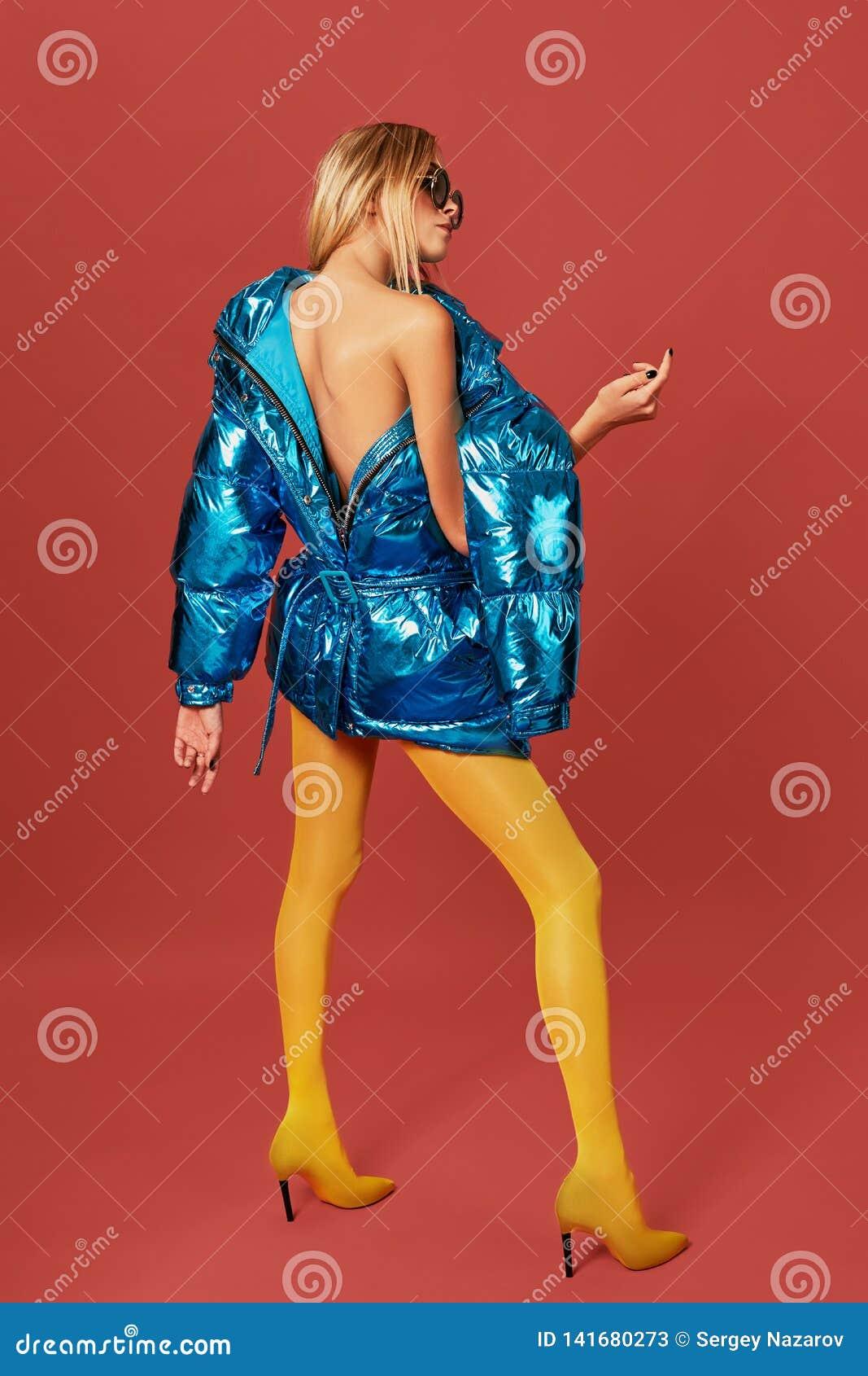 Den härliga blonda flickan poserar för kameran i ett omslag, påklädd tillbaka tillbaka sikt