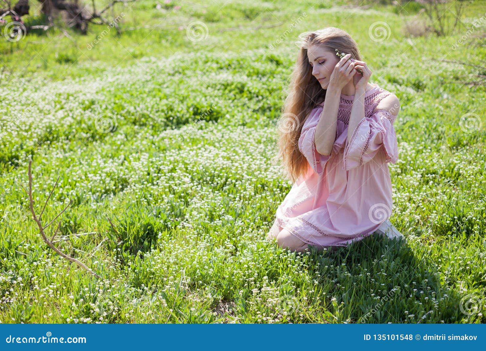 Den härliga blonda kvinnan samlar blommor för garnering