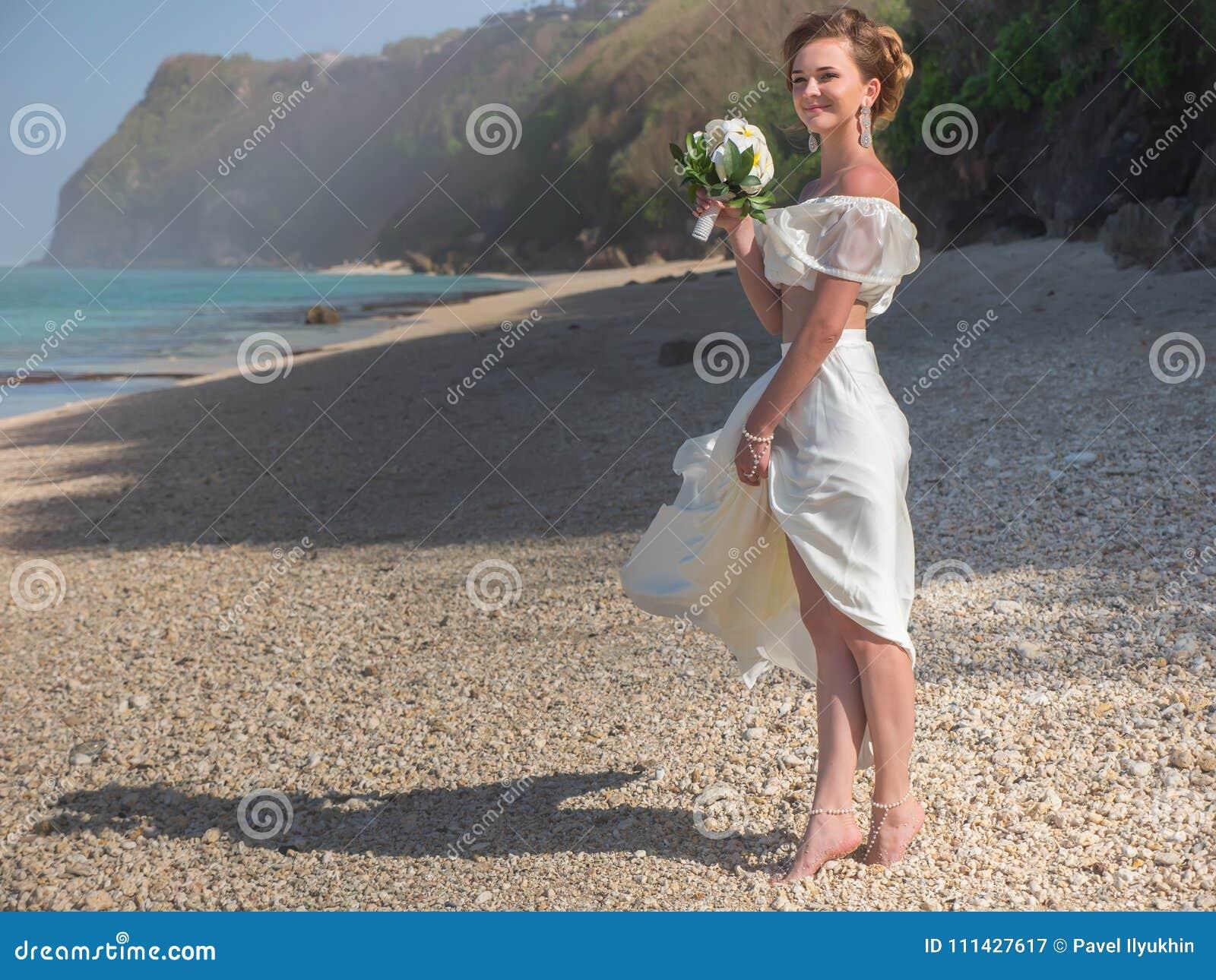 Den härliga bruden att gifta sig på stranden, Bali bröllop för brudceremoniblomma