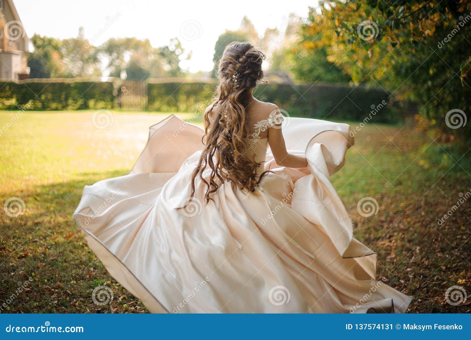 Den härliga bruden i en vit bröllopsklänning som kör i, parkerar